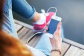 Fotografie Junge Frau sitzt auf Pier ein Smartphone halten