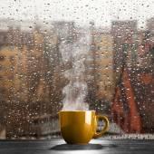 Kouřící šálek kávy na deštivý den