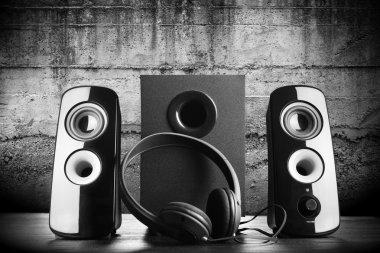 Modern black sound speakers and headphones on dark background stock vector