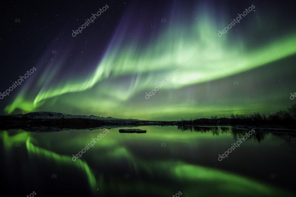Northern lights blazing over lake
