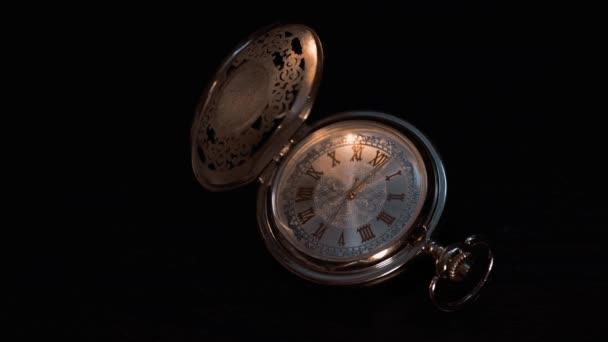silberne Taschenuhr aus nächster Nähe auf schwarzem Hintergrund