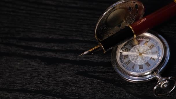 Taschenuhr und Füllfederhalter aus nächster Nähe auf einem schwarzen Holztisch