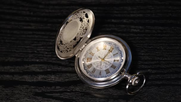 silver pocket watch close up on a black wooden table