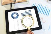Kézi Nagyító, fent a tabletta-val pénzügyi diagramos jelentés