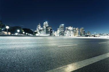 Empty road and illuminated modern cityscape