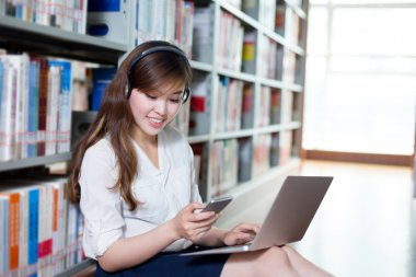 female student using laptop and mobile phone in library