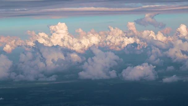 pohled z okna letadla na závoj mraků a na zemský povrch