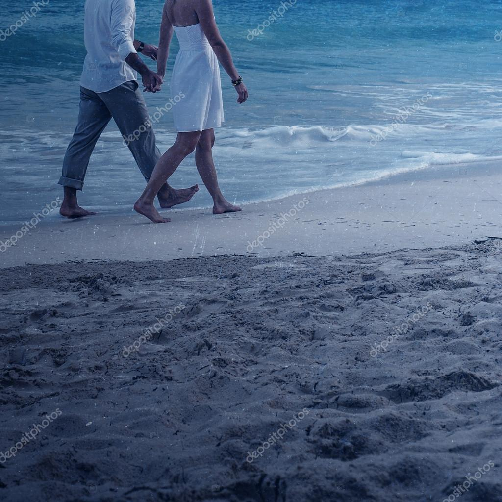 Couple walking on the beach in the moonlight