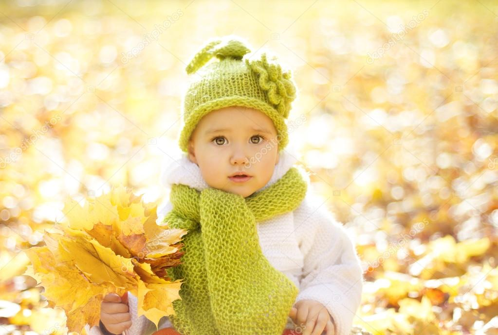 Autumn Baby Portrait In Fall Yellow Leaves, Little Child In Woolen Hat, Beautiful Kid in Park Outdoor, Knitted Clothing for October Season