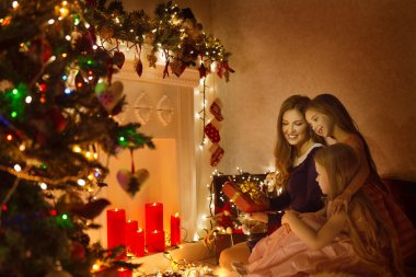 Christmas Family Woman Portrait, Mother And Daughters Celebrate Holiday, Opening Present Gift Box In Room Decorated By Xmas Tree and Candles Lights