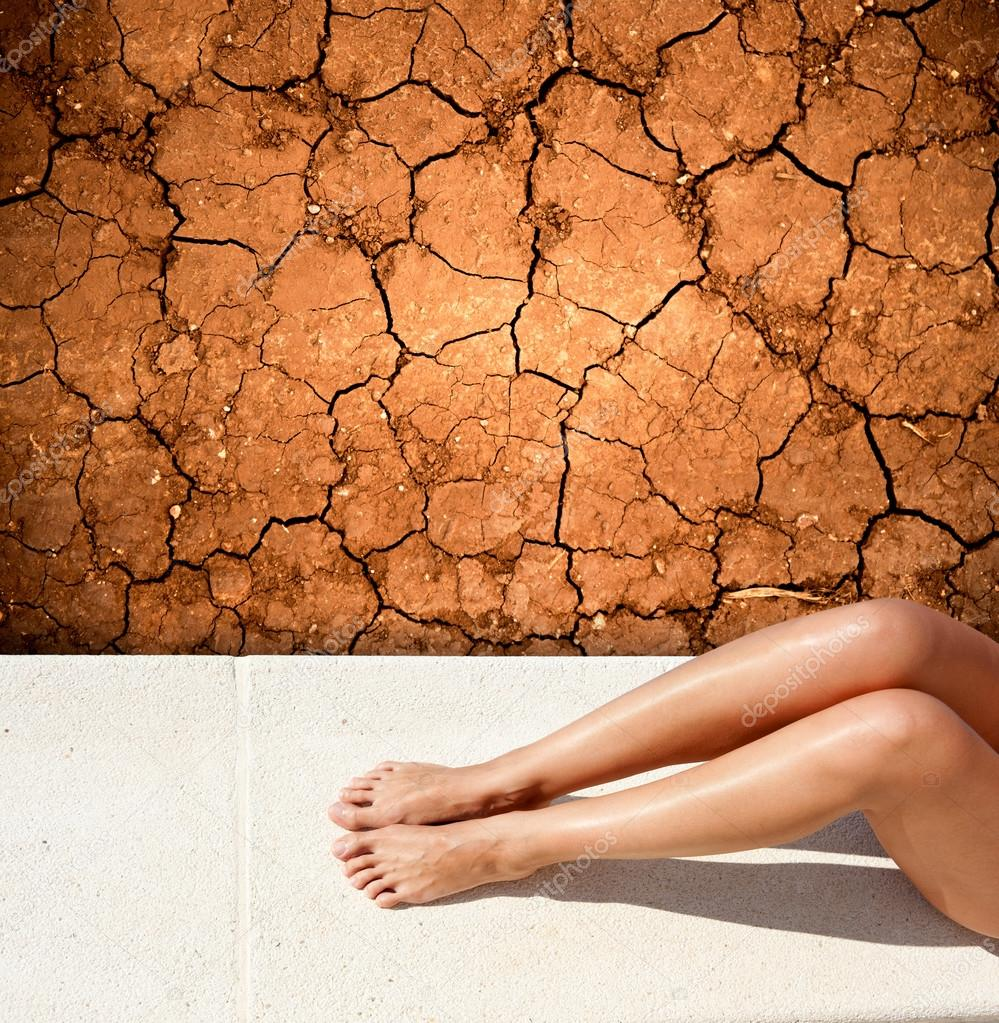 Sunbathing woman lying by a dried up land