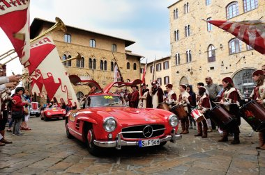 A red Mercedes 300 SL W 198, followed by a red Maserati 150, takes part to the 1000 Miglia classic car race