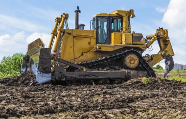 Bulldozer tractor works at moving soil