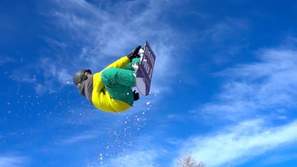 Snowboardista dělá trik proti modré obloze