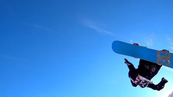 Snowboardista, skákání přes slunce v snowpark na krásný slunečný den