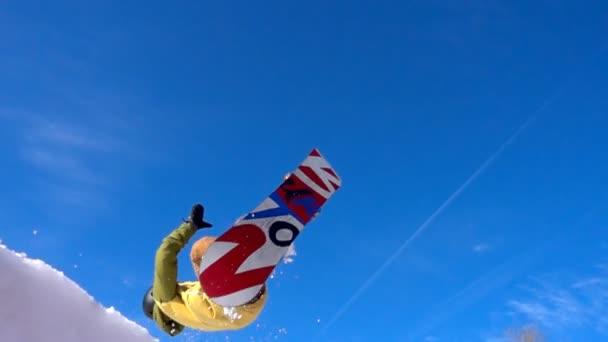 Snowboardista skákat vysoko nad slunné modrá obloha
