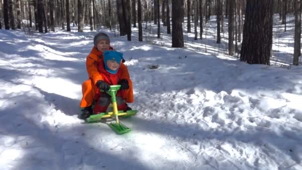 Happy kids ride on snowmobile