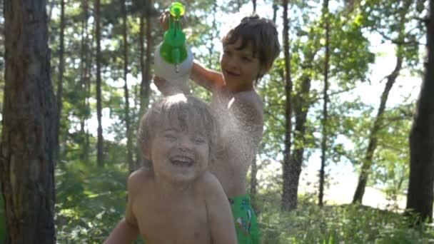 Junge Bewässerung sein kleiner Bruder vom Spritzgerät an heißen Sommertag