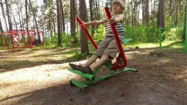 Junge trainiert auf Spielgeräten im Freien.