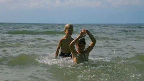 Kinder machen Spritzer im Meer