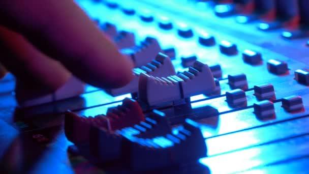 Direttore del suono lavorando sulla console di mixaggio professionale audio