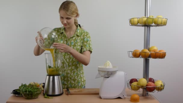 Žena, aby zelený koktejl s pomerančovým džusem v mixéru