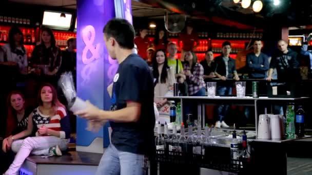 Bartender  juggles bottles behind the cocktail bar.