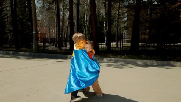 Boy in superhero costume hugging his younger brother