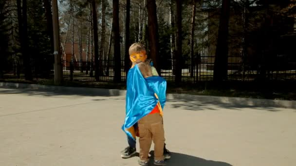Boy in superhero costume taking little brother in his arms