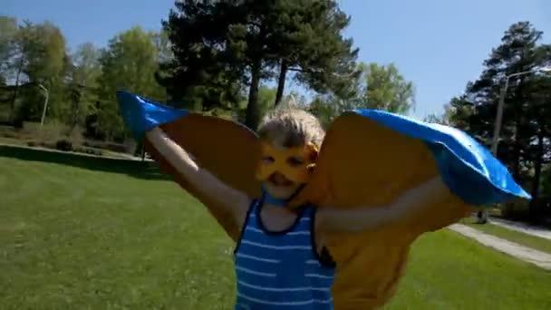 fiatal fiú a szuperhős jelmezben a parkban