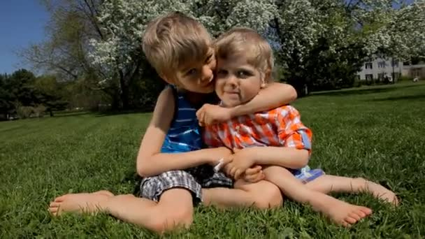 Two happy little brothers hugging on green grass