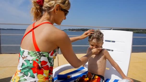 happy mother applying sunscreen on the face and body of little kid