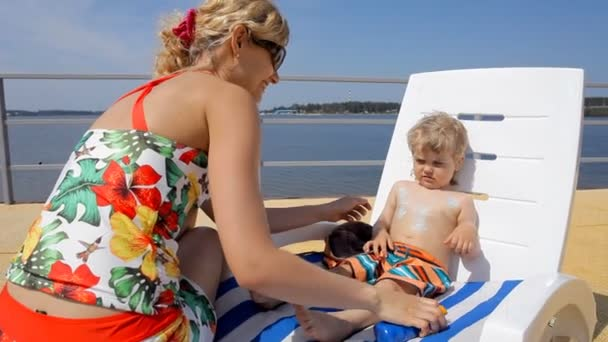 happy mother applying sunscreen on little kid sitting in chair