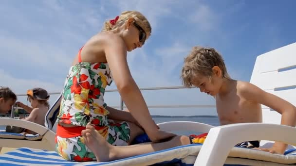 Young woman applying sun block on the legs of little boy.