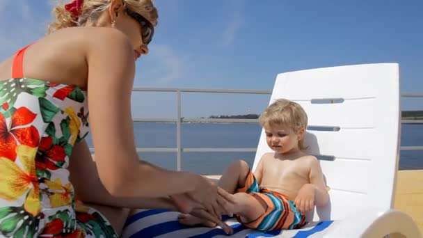 happy mother applying sunscreen on the body of her little boy