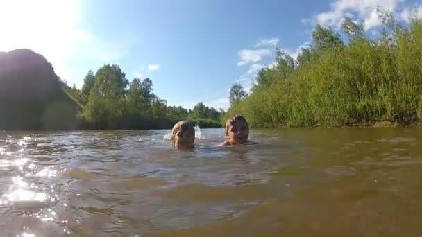 Mladí chlapci, koupání v řece v krajině. Šťastné děti hrají ve vodě