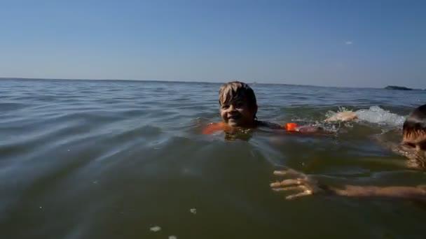 Kinder vergnügen sich im Wasser im Freien. glückliche kleine Jungen schwimmen und tauchen im Meer.