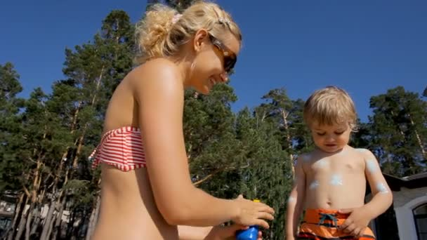 happy beautiful mother applying sunscreen on her little child boy