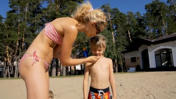 Mother and son applying sun screen lotion on the beach. Healthy sunbathing.