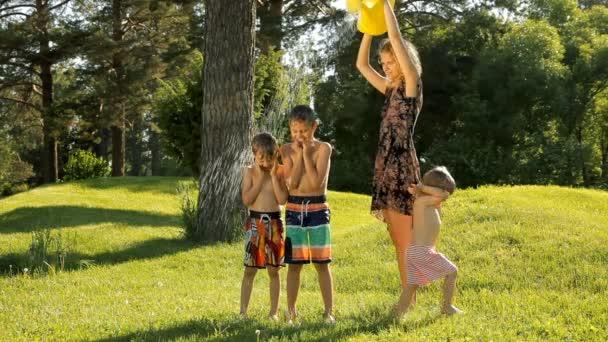 Mutter gießt Wasser aus einer Gießkanne auf glückliche Kinder in grünen park