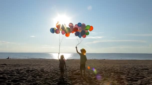 kids having fun jumping with balloons on the beach in sunny day