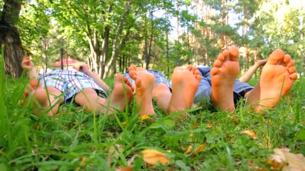 Barefoot feet of three little boys on green grass
