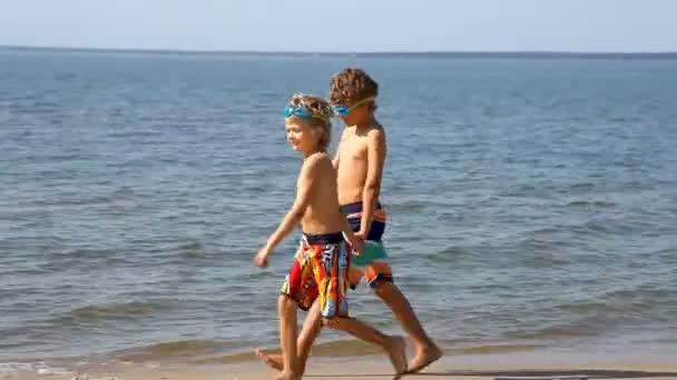 Chlapci, které drží ruce a spusťte na pláži
