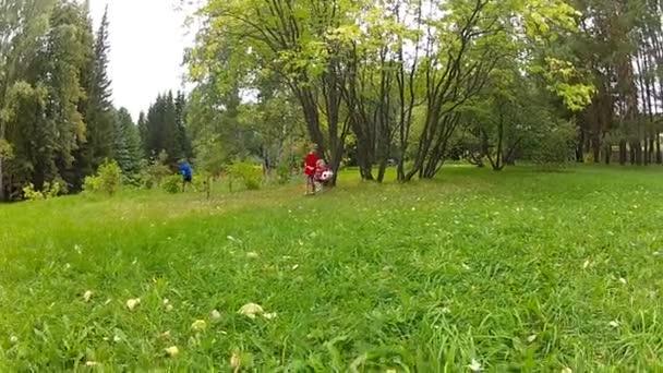 Roztomilý mladý bělošský kluky hrát fotbal v zahradě
