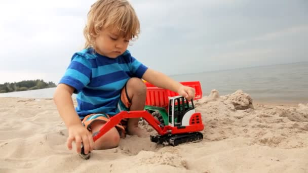 cute child loads sand with the help of toy excavator in the truck
