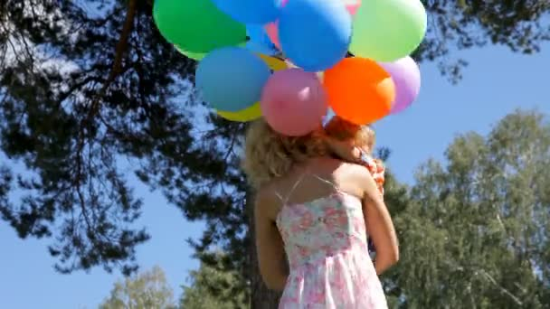 happy mother with little kid spinning with colorful balloons