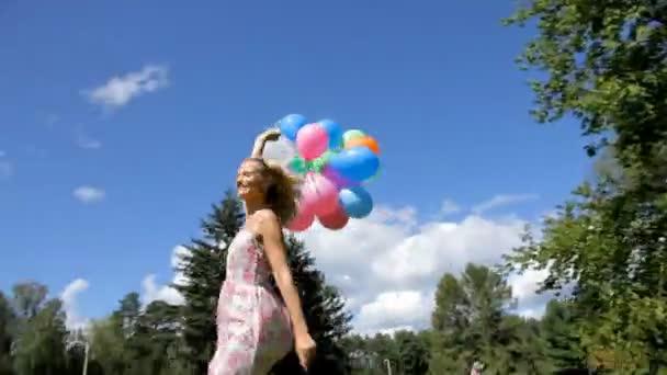 Mladá žena vesele točí s barevnými balónky