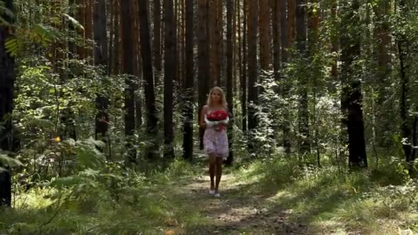 Young woman with bouquet of red roses walking in forest
