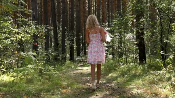 Young girl with bouquet of flowers walking in forest