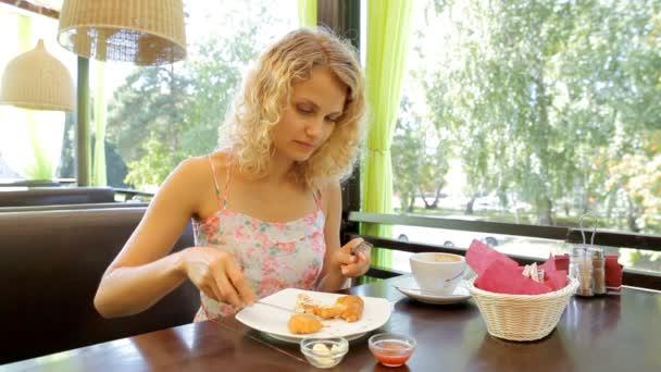 Gyönyörű szőke nő evés ízletes reggeli a kávézó